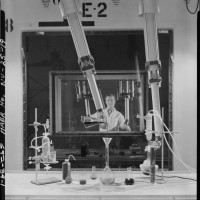 Worker manipulating small glass objects in the hot bay with manipulator arms. Photographer unknown, ca. 1969. Repository: Library of Congress.